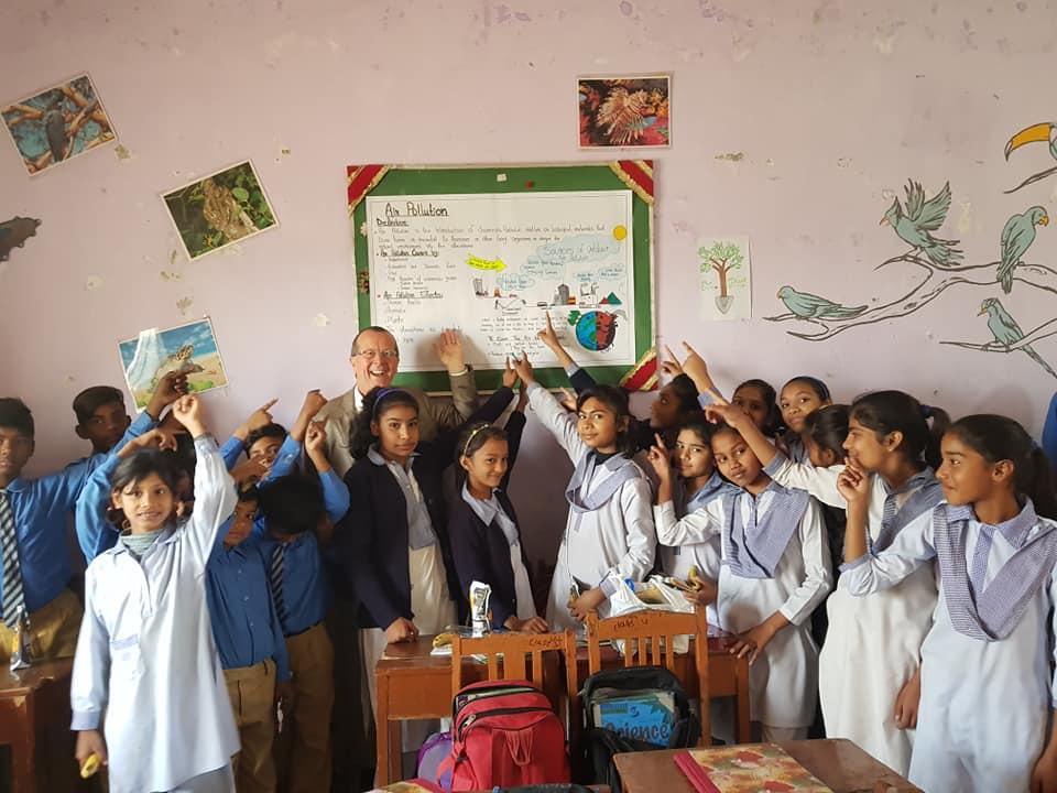 Pakistanische Schulklasse mit dem deutschen Botschafter Herrn Martin Kobler vor einem Schulplakat